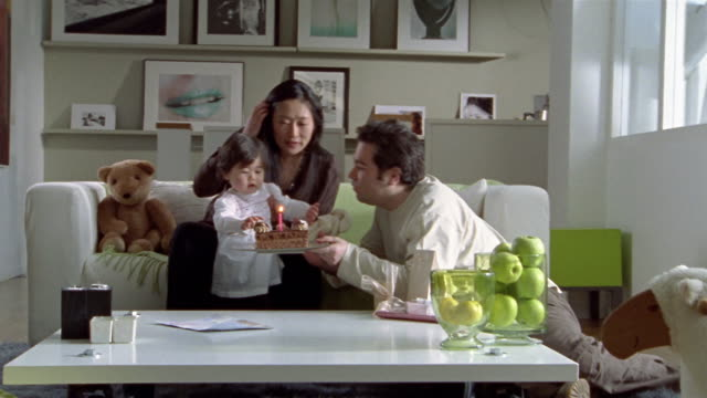 vidéos et rushes de wide shot man and woman with child gathered around table/ zoom in medium shot man lifting cake with one candle for baby to blow out - zoom avant