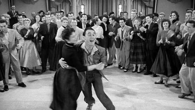 1956 wide shot man and women swing dancing as other couples watch in background - tipo di danza video stock e b–roll