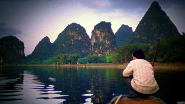wide shot man crouching on bow of riverboat and steering with stick / rock formations in background / li river, china - li river stock videos & royalty-free footage