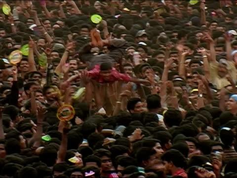 vídeos de stock, filmes e b-roll de wide shot man crowd surfing as crowd cheers at the thrissur pooram elephant festival / thrissur, kerala, india - jogando se na multidão