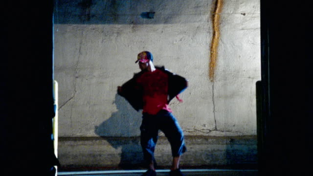 vidéos et rushes de wide shot man dancing against concrete wall and exiting/ woman entering and dancing - breakdance