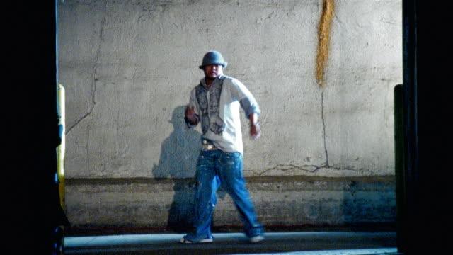 vídeos de stock e filmes b-roll de wide shot man dancing against concrete wall/ man exiting as another man enters and dances - insulano do pacífico