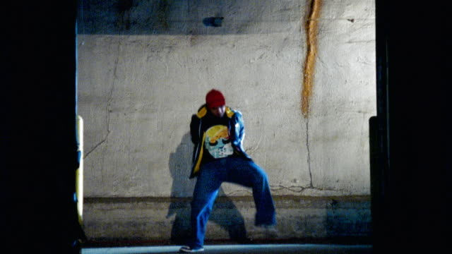Wide shot man dancing against concrete wall/ other man entering, pushing first man out of the way, and dancing