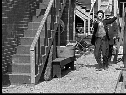 vídeos de stock, filmes e b-roll de 1918 b/w wide shot man dancing in alley as policeman pursues him - posição de combate