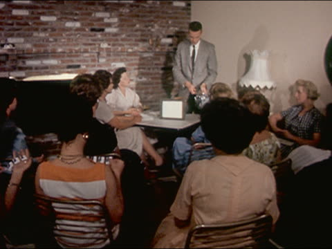 1962 wide shot man demonstrating geiger counter to group of suburban women / nevada / audio - contatore geiger video stock e b–roll