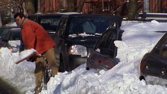 wide shot man digging car out of snow / pausing for breath / digging again - 掘る点の映像素材/bロール