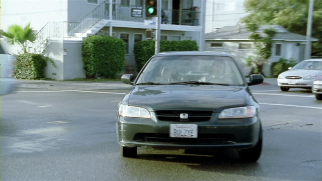 wide shot man driving sedan with license plate that says 'bulzye' / making turn at intersection - number plate stock videos & royalty-free footage