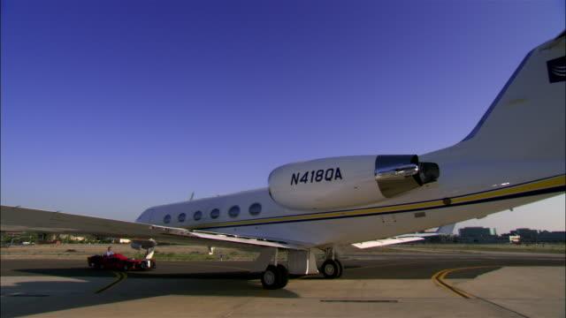 vidéos et rushes de wide shot man driving vehicle and pushing private jet on airport runway / long beach, california, usa - piste d'envol