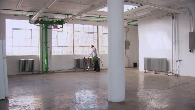 wide shot man entering empty loft space, setting down bicycle, walking and looking around/ brooklyn, new york - loft apartment stock videos & royalty-free footage