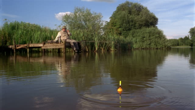 wide shot man fishing at end of dock in lake / float bobbing in foreground / man reeling in line - fishing line stock videos & royalty-free footage
