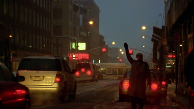 Wide shot man hailing taxi on snowy city street at dusk / New York City