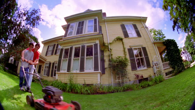 fisheye wide shot man helping boy push lawn mower in yard / house in background - lawn mower stock videos and b-roll footage
