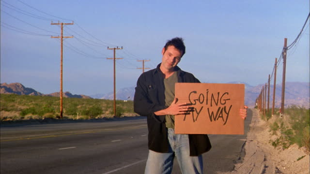 Wide shot man hitchhiking by desert highway holding 'Going My Way' sign