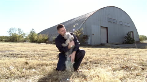 vídeos de stock, filmes e b-roll de wide shot man holding schnauzer and smiling at camera - terrier