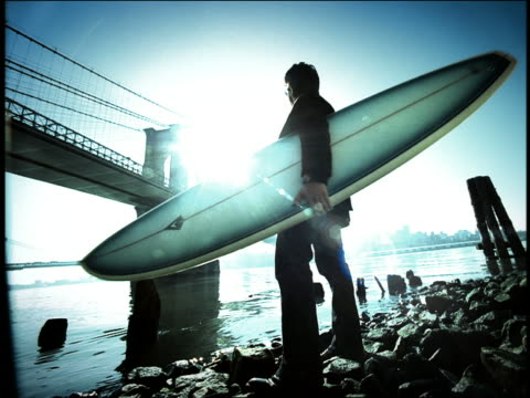 blue high contrast wide shot man holding surfboard on bank of east river turns toward brooklyn bridge / nyc - high contrast stock videos & royalty-free footage