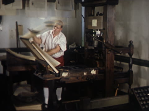 1957 recreation wide shot man in colonial dress operating 18th century printing press / examining paper - collant video stock e b–roll