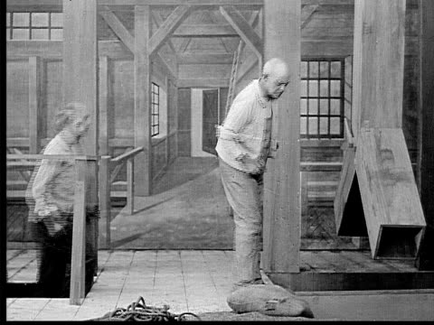 1909 b/w wide shot man in grain mill/ tycoon and women coming up steps to visit mill  - 麻袋点の映像素材/bロール