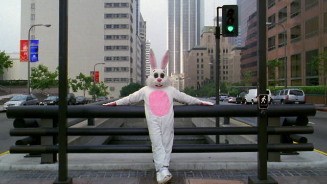 wide shot man in rabbit costume leaning against bridge railing with office buildings in background / los angeles, ca - full length stock videos & royalty-free footage
