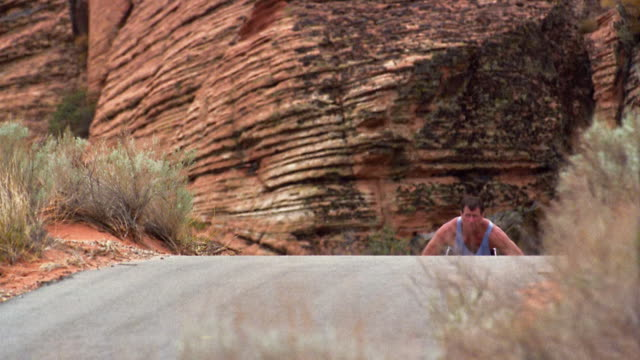 wide shot man in racing wheelchair climbing hill in red rock canyon - adaptive athlete stock videos and b-roll footage