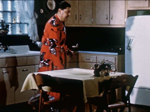 1951 Wide shot man in robe sneaking into dark kitchen for midnight turkey snack from refrigerator / AUDIO