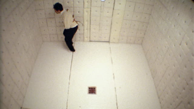 Wide shot man in straitjacket bouncing off walls and jumping around in padded room