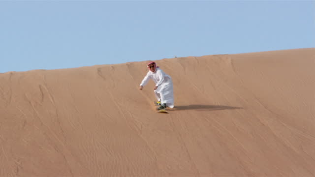 vídeos de stock, filmes e b-roll de wide shot man in traditional middle eastern clothing sandboarding down dune and falling/ dubai - membro humano