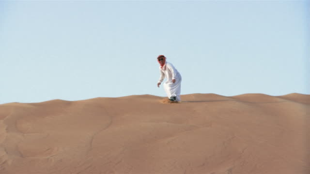 wide shot man in traditional middle eastern clothing sandboarding down dune/ dubai - 45 49 anni video stock e b–roll
