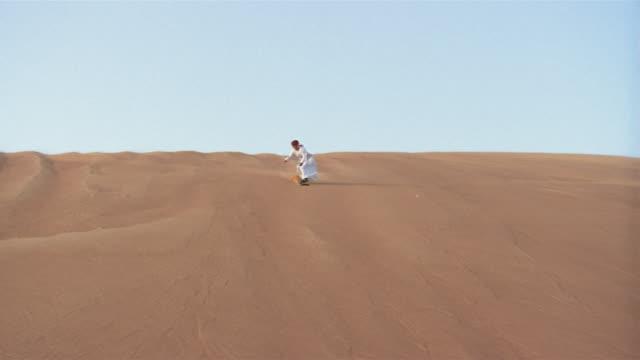 vídeos de stock, filmes e b-roll de wide shot man in traditional middle eastern clothing sandboarding down dune/ dubai - membro humano
