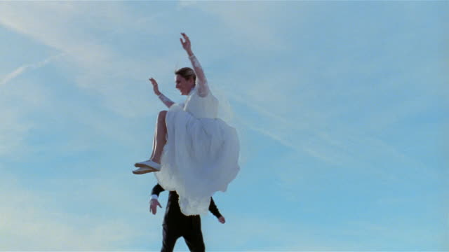 Wide shot man in tuxedo and woman in wedding dress jump up and down on trampoline doing various kicks in midair