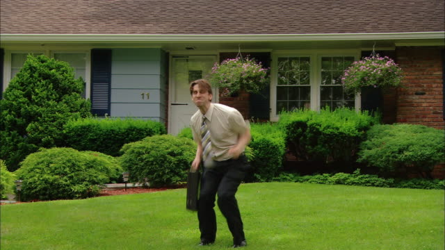 wide shot man jumping up and throwing briefcase into the air / duckwalking across lawn and falling to his knees - punching the air stock videos & royalty-free footage