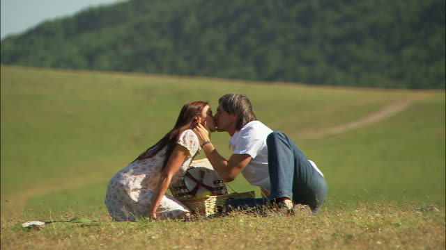 wide shot man kissing woman over picnic basket while sitting on ground/ couple leaning back smiling/ couple talking/ umbria - picnic basket stock videos and b-roll footage