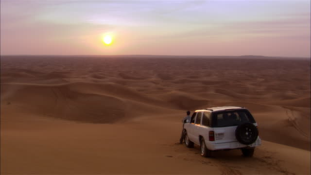 wide shot man leaning on suv looking out over desert dunes towards sunset - 40 44歳点の映像素材/bロール