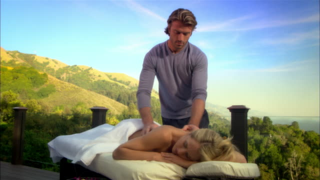 vídeos y material grabado en eventos de stock de wide shot man massaging woman on massage table/ monterey country, california, usa - massage table