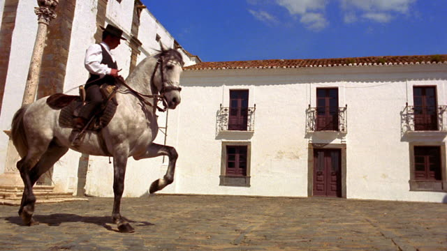 Wide shot man on Lusitano horse doing dance-like movements (dressage) in courtyard / Monsaraz, Portugal