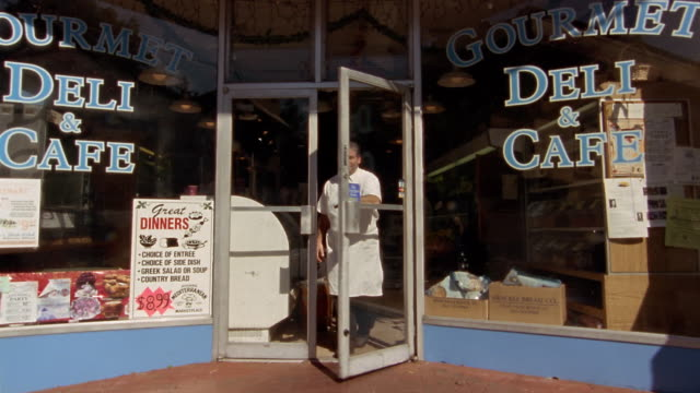 wide shot man opening door of delicatessen and standing in doorway / looking up + down street - long island video stock e b–roll
