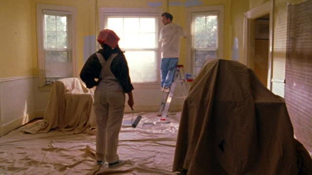 vídeos de stock e filmes b-roll de wide shot man painting walls + woman watching in drop cloth covered room - pano de protecção