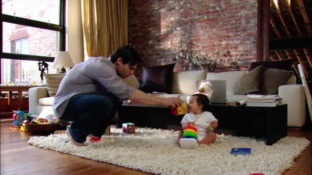 wide shot man playing with baby on living room floor / sitting on the sofa and using laptop computer - house husband stock videos & royalty-free footage