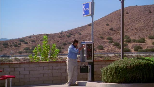 vídeos de stock e filmes b-roll de wide shot man putting coins in slot and using roadside pay phone - lista telefónica