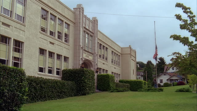 stockvideo's en b-roll-footage met wide shot man raising flags on flagpole in front of school / astoria, oregon - school building