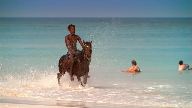 wide shot man riding fast horse on beach/ harbor island, bahamas - アフリカ系カリブ人点の映像素材/bロール
