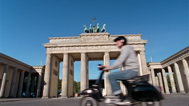 wide shot man riding past brandenburger gate on vespa / berlin, germany - scooter stock videos & royalty-free footage