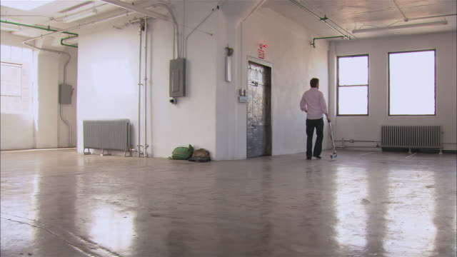 wide shot man riding push scooter around empty loft space/ other man walking in, standing by window/ man on scooter continues riding/ brooklyn, new york - loft stock videos and b-roll footage