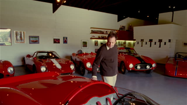 wide shot man running his hands along the side of red sportscar in garage - stroking stock videos and b-roll footage