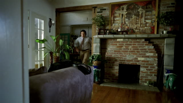 Wide shot man rushing into living room and grabbing bag / getting keys out of pocket / leaving for work