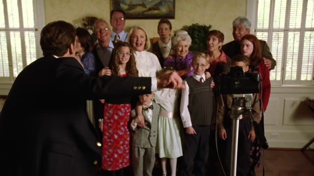 Wide shot man setting camera timer for photo of multi-generational family and rushing to join them
