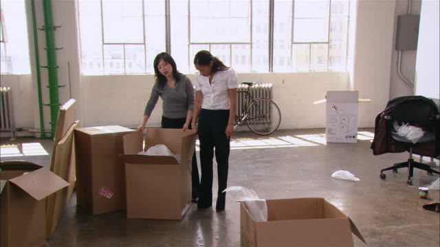 Wide shot man setting up printer in new office space as other man looks on/ pan two women looking in large box/ woman moving box/ Brooklyn, New York