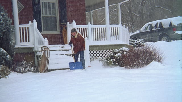 Wide shot man shoveling snow from front walk / stoping and posing