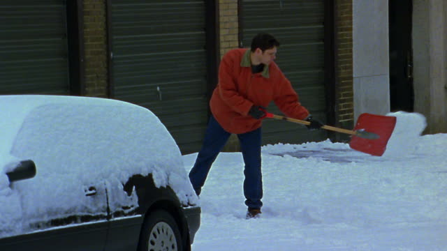 Wide shot man shoveling snow