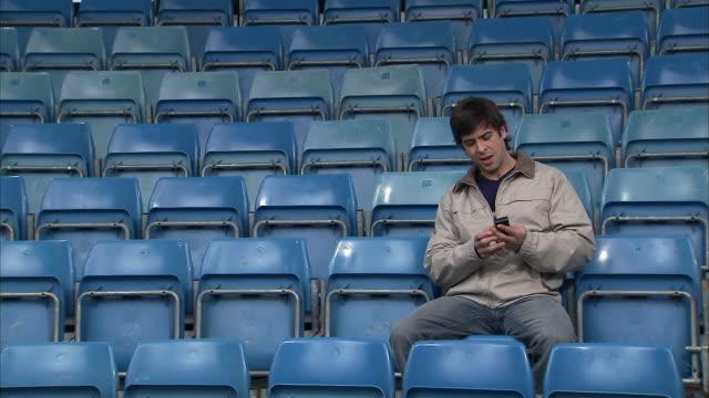 vídeos de stock e filmes b-roll de wide shot man sitting in empty stadium/ man answering mobile phone/ england - assento