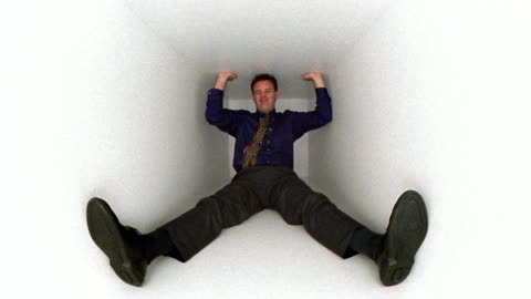 wide shot man sitting in white box with legs splayed, pressing against top with hands, making strained face - trapped stock videos & royalty-free footage
